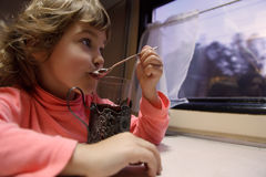 Little girl in train car drinks tea Royalty Free Stock Photography