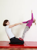 Little girl and a trainer are doing an exercise stock photos