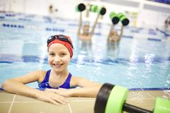 Little girl training in the pool stock photography