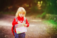Little girl travel hiking in nature looking at map. Travel concept Stock Image