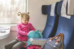Little girl travel by train. Kid sitting in comfortable chair and looking in backpack. Things to take with on railroad trip with stock images