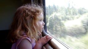 Little girl traveling railway. Beautiful little girl looking through the train window while traveling railway stock footage