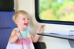 Little girl traveling by train Stock Images