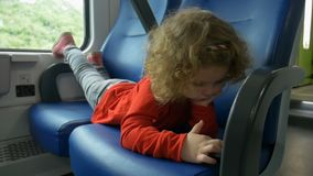 Child in train looks at smartphone. Little girl is traveling by train and looks at smartphone stock video footage