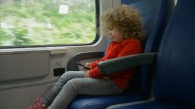 Happy little girl is traveling by train. Little girl traveling by train and using mobile phone stock video footage