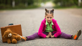 Little girl traveller on the road with a suitcase and a Teddy bear. aTrvel. Stock Photo