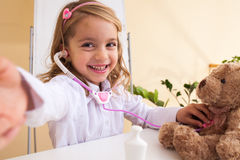 Little girl treats a toy bear and making selfie Stock Image