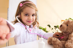 Little girl treats a toy bear and making selfie Stock Photography