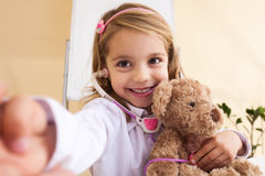 Little girl treats a toy bear and making selfie Royalty Free Stock Photo