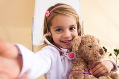 Little girl treats a toy bear and making selfie Stock Images