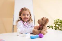 Little girl treats a toy bear Stock Photos