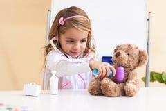 Little girl treats a toy bear Stock Photo
