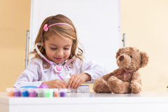 Little girl treats a toy bear Stock Images