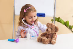 Little girl treats a toy bear Royalty Free Stock Photography