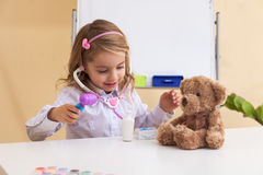 Little girl treats a toy bear Royalty Free Stock Photo