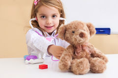 Little girl treats a toy bear Stock Photography