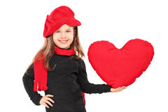 Little girl in trendy clothes holding a big red heart Royalty Free Stock Photos