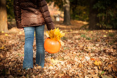 Little girl trick or treating, picking leaves Royalty Free Stock Image