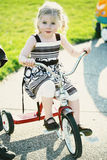 Little girl on tricycle. Little girl wearing summer dress riding red tricycle on a sunny day Stock Images