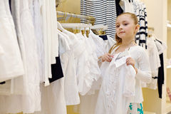Little girl tries on blouse in clothing store Stock Image