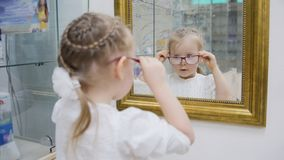 Little Girl Tries New Glasses Near Mirror - Shopping In Ophthalmology Clinic Royalty Free Stock Photo