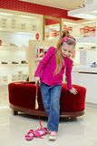 Little girl tries on new shoe Stock Photo
