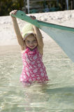 Little girl tropical beach FUN boat royalty free stock photography