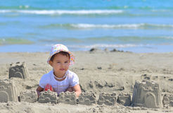 Little girl at tropical beach making sand castle in summer Stock Image