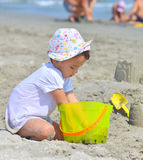 Little girl at tropical beach making sand castle in summer Stock Photos