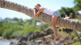 Little girl at tropical beach sitting on palm tree during summer vacation. Adorable little girl at tropical beach sitting on palm tree during summer vacation stock footage