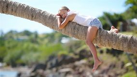 Adorable little girl at tropical beach sitting on palm tree during summer vacation. Little girl at tropical beach sitting on palm tree during summer vacation stock video footage