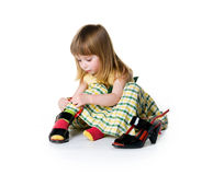 Little girl try on big shoes Stock Photos