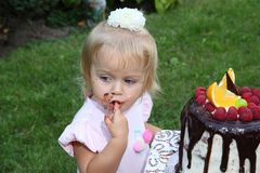 A little white-haired girl of two years is trying a birthday cake. Little girl celebrating second birthday. Royalty Free Stock Photography