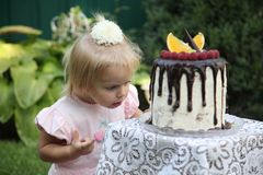 A little white-haired girl of two years is trying a birthday cake. Little girl celebrating second birthday. Royalty Free Stock Photos