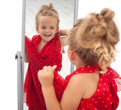 Little girl trying dress in front of mirror royalty free stock photography