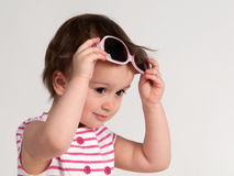 Little girl trying on glasses Stock Images