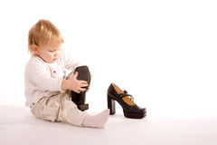 Little girl trying her mother's shoes on the floor Stock Photography