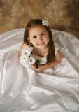 Little girl trying on mommy's wedding dress Stock Photos