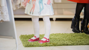 Little girl trying on pink shoes in shop for kids Royalty Free Stock Photo