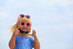 Little girl trying on sunglasses at sky Stock Image