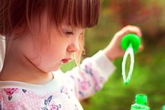 Little girl trying to blow soap bubbles royalty free stock images