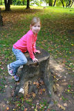 A little girl trying to climb up a tree trunk Stock Image