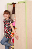 Little girl trying to close messy closet Stock Image