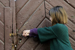 Little girl trying to open old door Stock Photo
