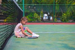 Little girl trying to play tennis on outdoor court Stock Photos