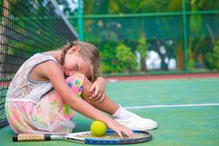 Little girl trying to play tennis on outdoor court Stock Photo