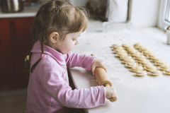 The little girl is trying to roll out the dough, concentration Royalty Free Stock Images