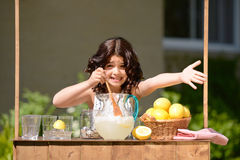 Little girl trying to sell lemonade. At her stand royalty free stock photography