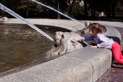 Little girl trying to touch water in city fountain. royalty free stock photography