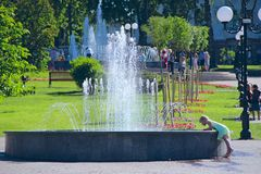 Little girl trying to touch water in city fountains. People have a rest in city park with fountains. Sunny summer day Royalty Free Stock Images